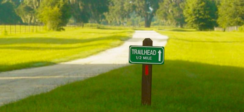 trailhead sign and paved trail