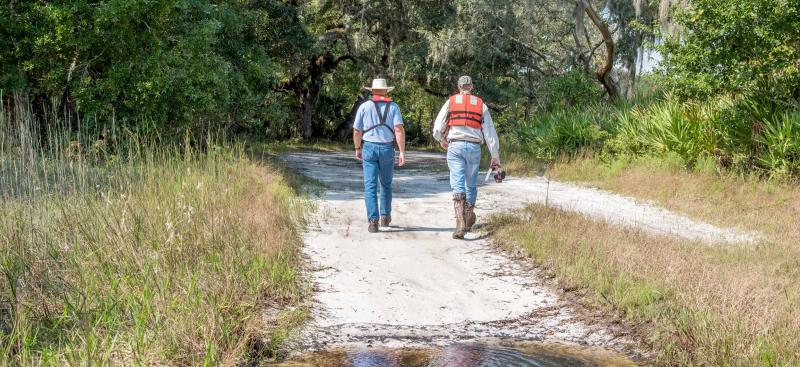 District staff walking on sandy trail near Withlacoochee River