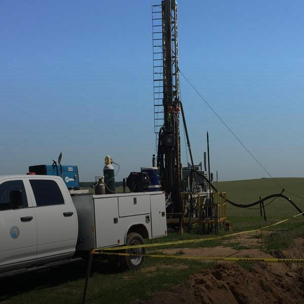 District truck and drill rig at well site